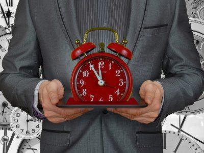Postać mężczyzny trzymającego zegarek.